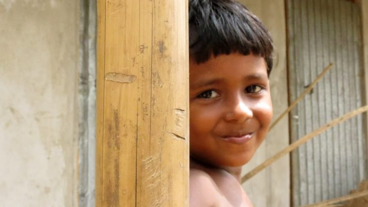A boy behind a bamboo post